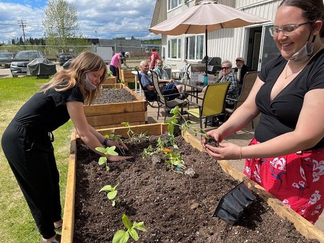 Volunteers planting in raised beds at Grace Manor